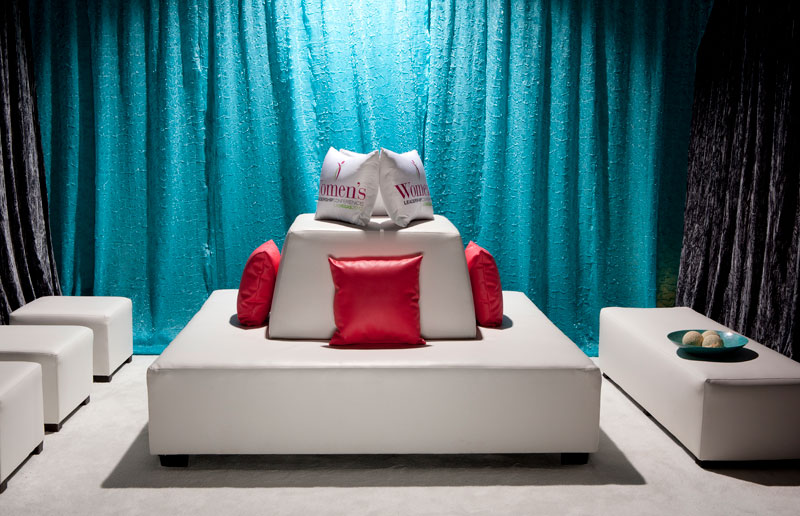 Turquoise backdrop with white vegan leather ottoman with back, benches, ottomans and colorful pillows