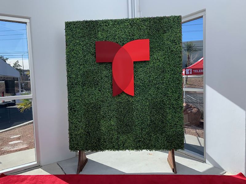 hedge back wall with custom logo feature for photos at grand opening reception
