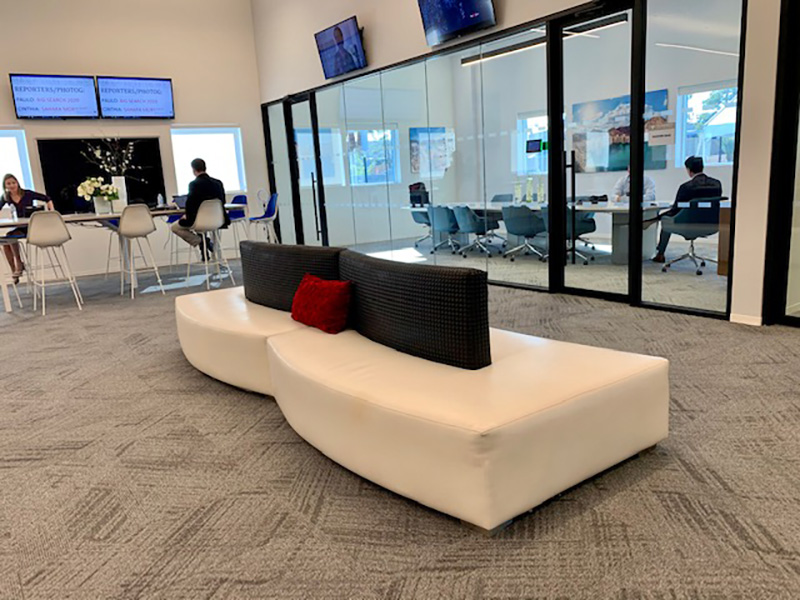 Somers furniture rental installation of White serpentine sectional seating with black accents at telemundo grand opening