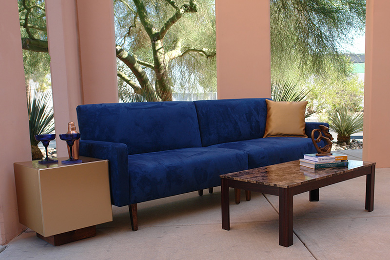 Blue suede sofa with cube charging tables and brown marbel cocktail table outside