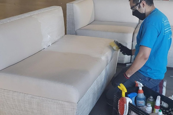Somers Furniture employee cleaning white outdoor sofa sectional peices