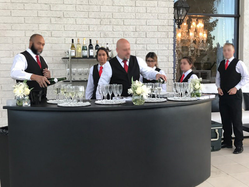 Bartenders behind a large circular bar and an etagere in black and steel with bottles and glasses arranged on it.