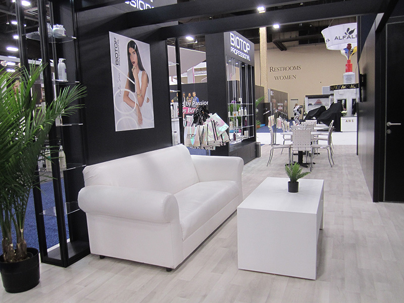 exhibit booth with white couch and table by somers furniture rental division  in las vegas