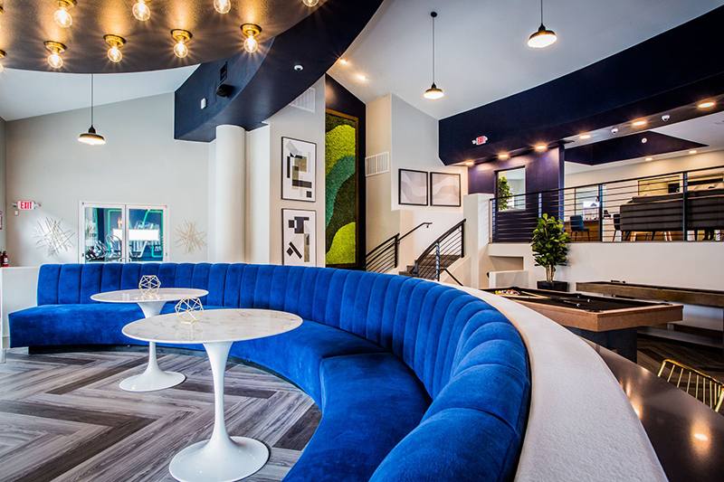 Las Vegas clubroom hosts a royal blue curved banquette with white dining tables by Somers Furniture