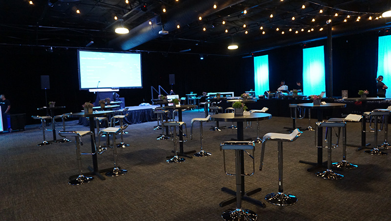 Wide view of dimly lit Las Vegas event space with pedestal tables, both round and rectangle with barstools, along with white tables and chairs in the dimly lit Las Vegas event space furnished by Somers Furniture rental division