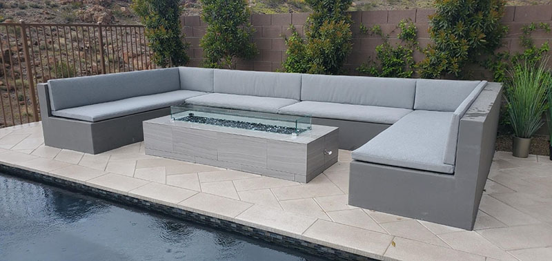 Tight seated sectional sofa in u-shape around fire pit by luxury residential pool