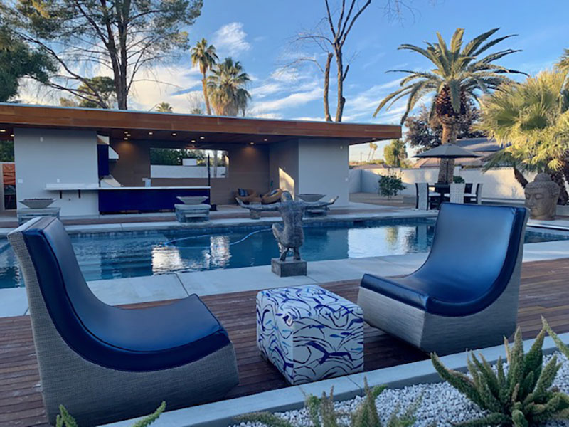 Lounging rockers in metallic blue silicon fabric with cushion side table by luxury residential pool