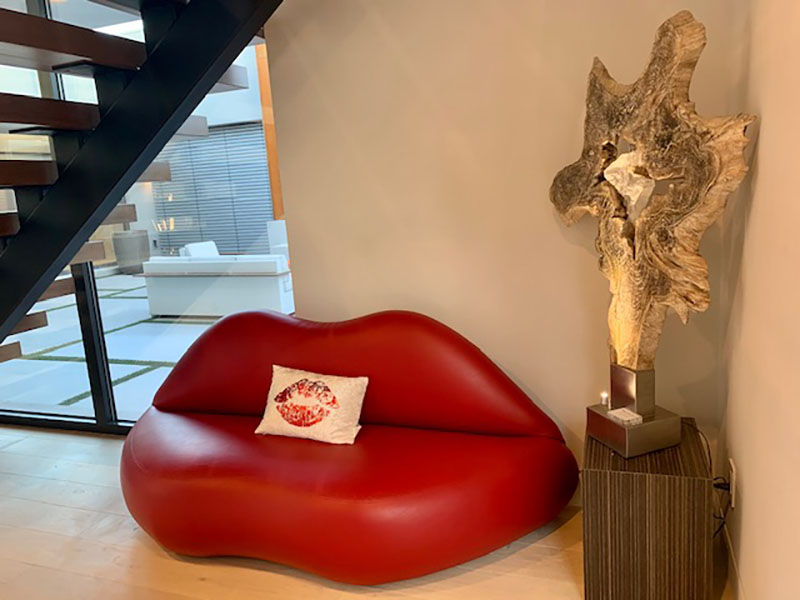 Red Lip Sofa placed in front the staircase and next to a statue in the foyer