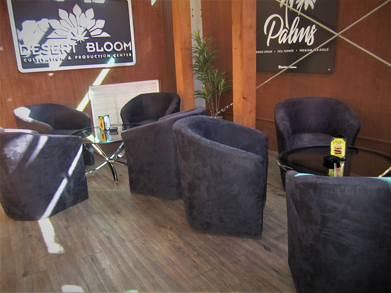 Black round horseshoe shaped suede chairs sitting in a circle with round glass table at nuwu in las vegas