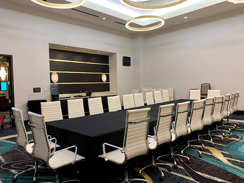 Professional meeting room with executive style office furniture including 15' conference table with charging stations and 18 white executive chairs