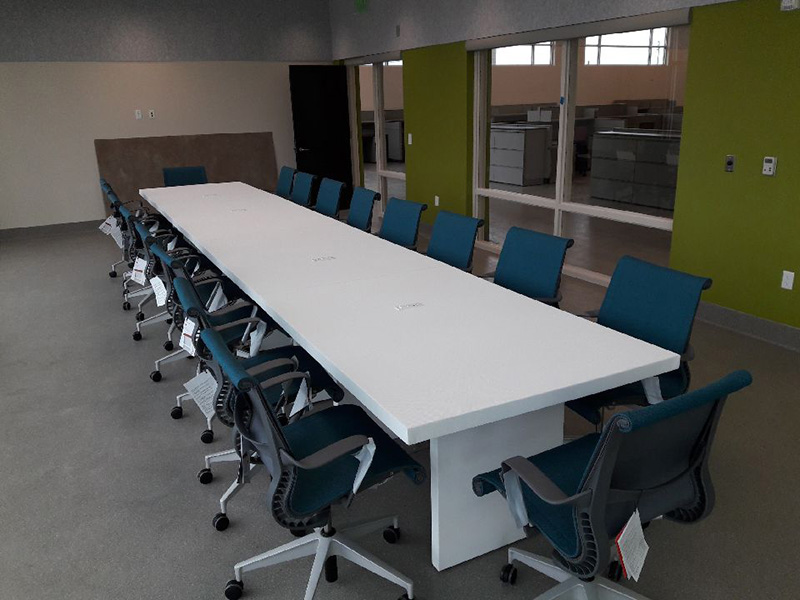 white charging conference table with teal chairs around it at Las Vegas Animal Foundation