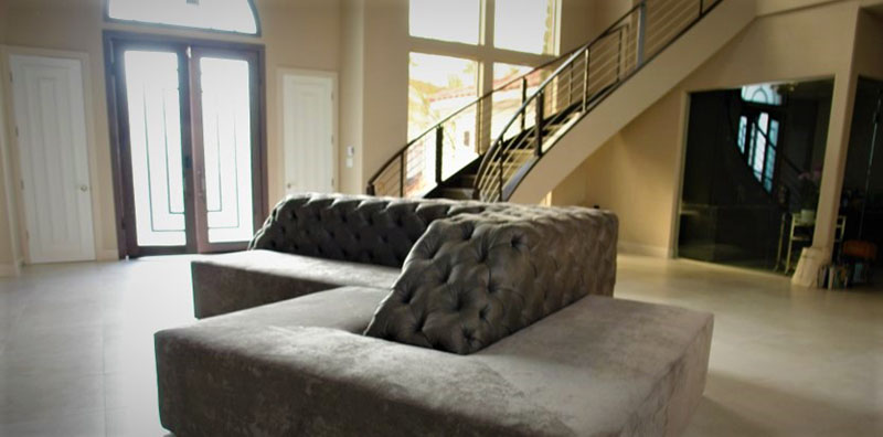 custom gray velvet tufted sectional in front of a grand staircase in luxury residence