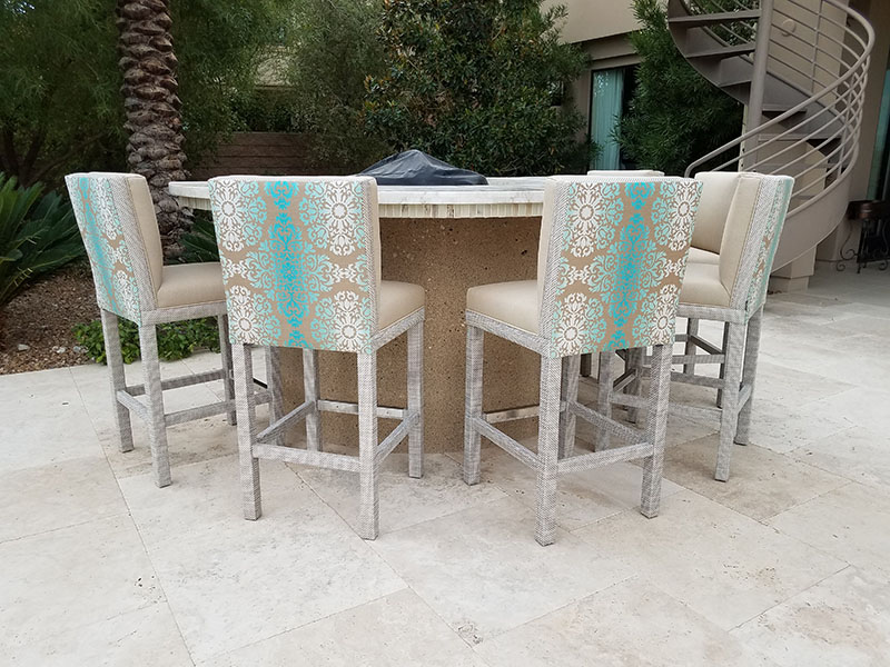 Tall barstools with cushioned seats and backs and fabric wrapped bases surround a round fire pit