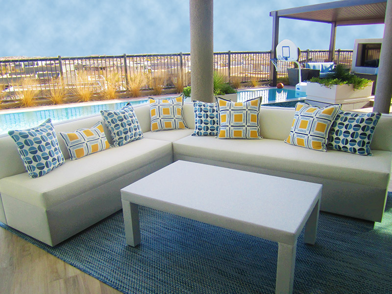 custom sized tightseated white and gray upholstered sectional accented with blue and yellow textured pillows and gray rectangle cocktail table outdoor fabric wrapped for durable and carefree living outside in Las Vegas