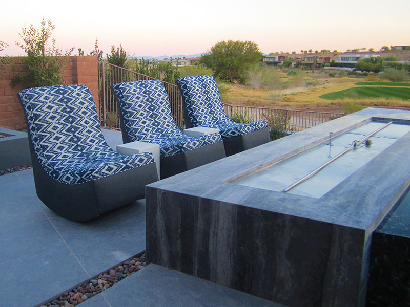 three rocking lounge chairs with a gray base and blue patterned fabric face a fire pit in las vegas