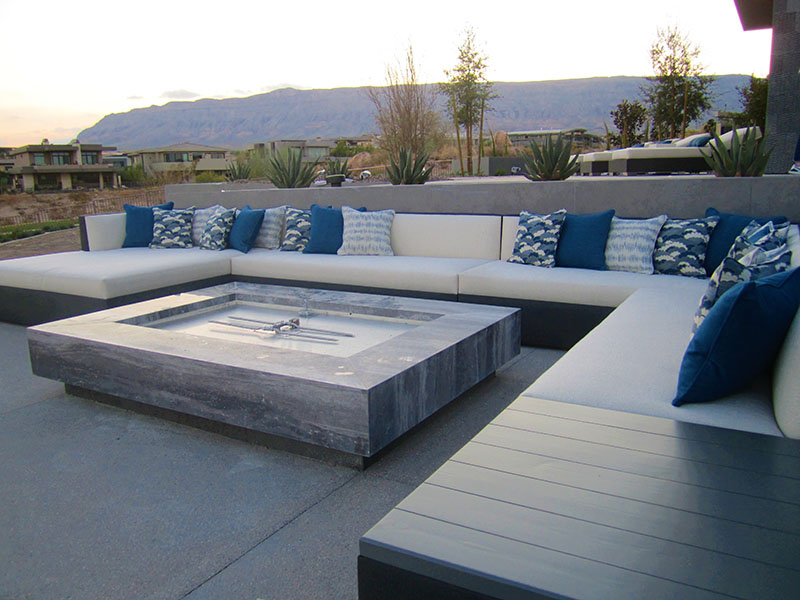 Custom built over-sized upholstered sectional surrounds a giant fire pit with blue pillows of different shapes, sizes and textures