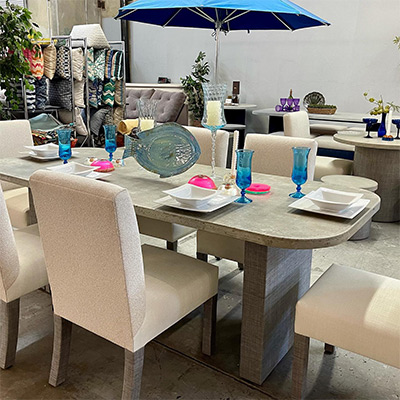 Somers Furniture showroom showing set table and chairs with pillows and umbrella in background